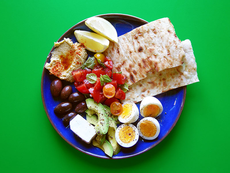 East Van Kitchen's Rustic Breakfast is a hearty + colourful way to start the day! Boiled eggs, bruschetta, avocado, toasted flatbread, hummus, olives + feta with a squeeze of lemon